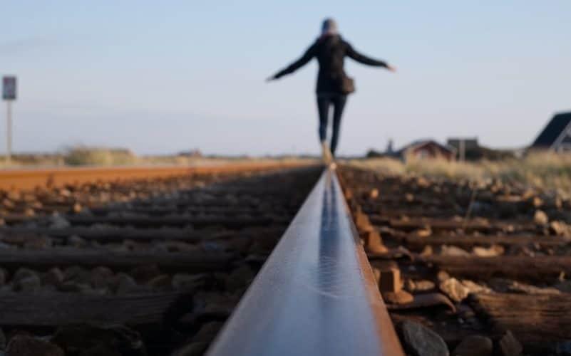 woman walking on train railway